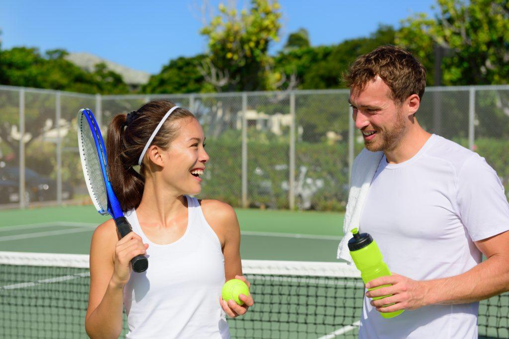 Coach Partner Scheme - Mixed tennis players smiling on the tennis court
